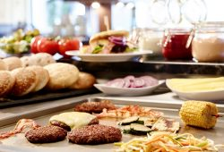 Burger Patties und Gemüse auf der Grillplatte