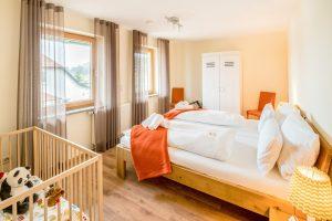 Schlafbereich mit Gitterbett im Ferienapartment Seerose