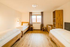 Kinderzimmer mit drei normalen Betten und Gitterbett in Familiensuite
