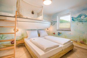 Kinderzimmer mit Doppelbett und Etagenbett in Schiffform im Fischerhaus