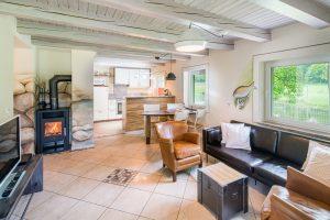 Wohnzimmer mit Blick auf Kamin und Küche